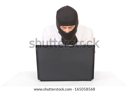 Man in black mask with computer looking at camera with evil view