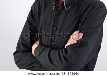 man in black shirt with crossed hands on chest
