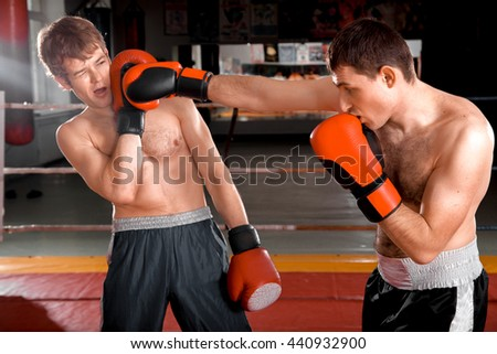 Man in black shorts is striking a blow to his opponent who leaning back
