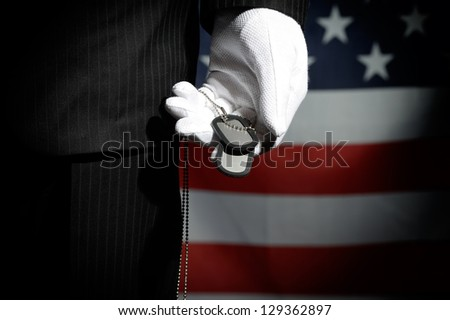 Man in black suit and white gloves with dog tag in hand on background of the US flag