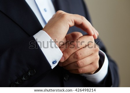 Man in black suit, correcting the sleeves of his shirt, close up - stock photo
