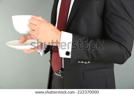 Man in black suit drinking coffee on grey background - stock photo