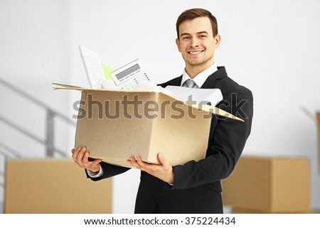 Man in black suit holding carton box full of office stationery in the room, close up - stock photo