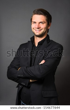 Man in Black Suit in front of a grey background looking happy - stock photo