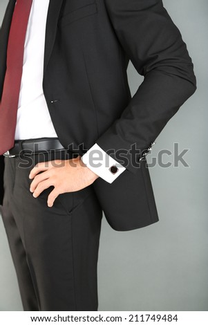 Man in black suit on grey background - stock photo