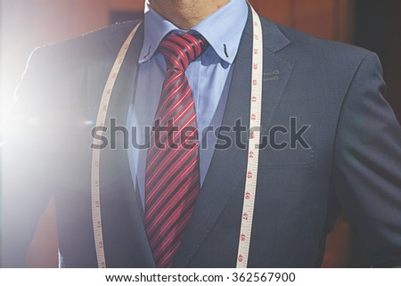 man in black suit with tie and measure tape. - stock photo