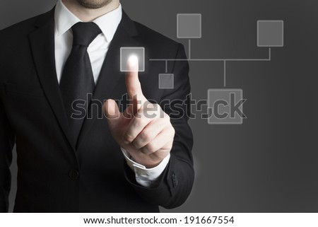 man in black suite pressing virutal button group - stock photo