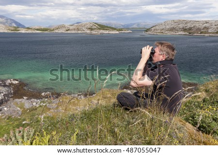 Man in black T-shirt sitting in grass on top on sunny day, looking around with binoculars. Helgeland archipelago, Norway.