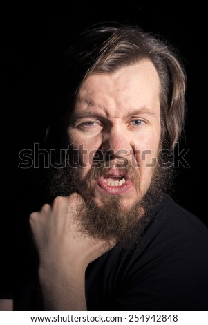 man in black with a theatrical grimace - stock photo