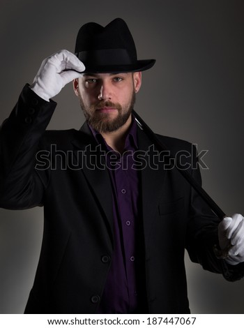 man in black with white gloves and hat in front of grey background