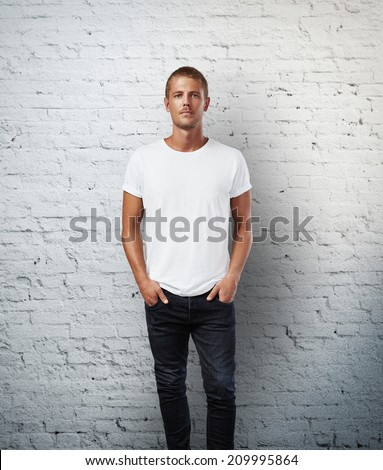 Man in blank t-shirt. Brick wall background - stock photo