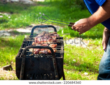Man in blue jeans and tshirt cooking marinated turkey shashlik on wooden skewer on the grill. Backyard party background. - stock photo