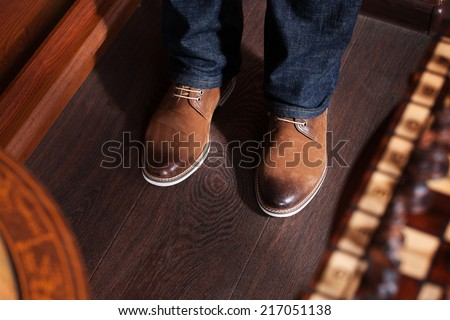 man in blue jeans and yellow boots standing on a dark floor - stock photo