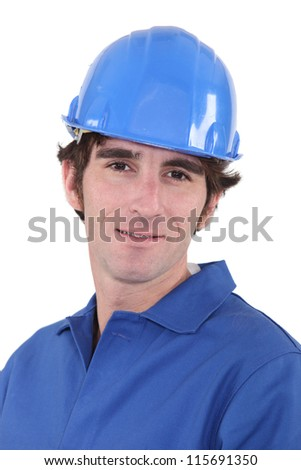 Man in blue overalls and hardhat - stock photo