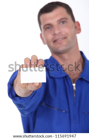 Man in blue overalls holding a business card left blank for your details
