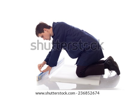 man in blue robe  draws a pencil on a sheet of paper on the floor - stock photo