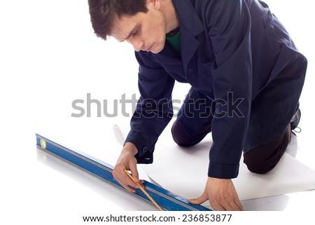 man in blue robe  draws a pencil on a sheet of paper on the floor