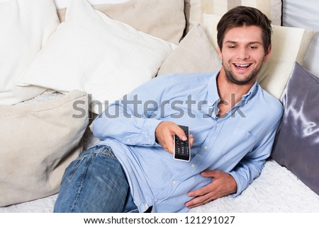 Man in blue shirt and jeans with remote control