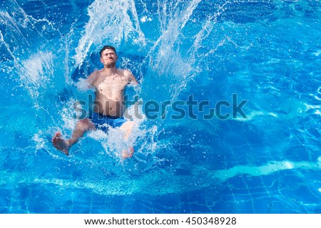 Man in blue trunks jumping in the pool with splashes