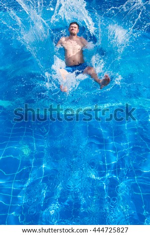 Man in blue trunks jumping in the pool with splashes, sunny. Toned