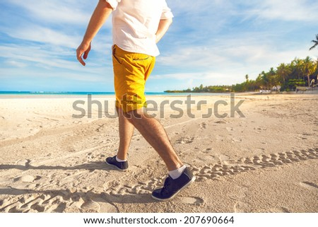 Man in bright yellow shorts white shirt and leather black sneakers walking at tropical beach with ocean blue water and palms, exotic view, bright colors. - stock photo