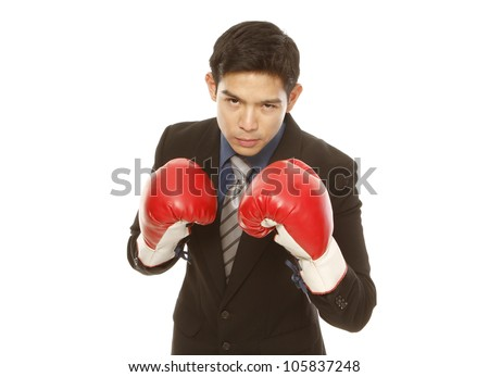 Man in business attire wearing boxing gloves in a fighting stance (on white) - stock photo