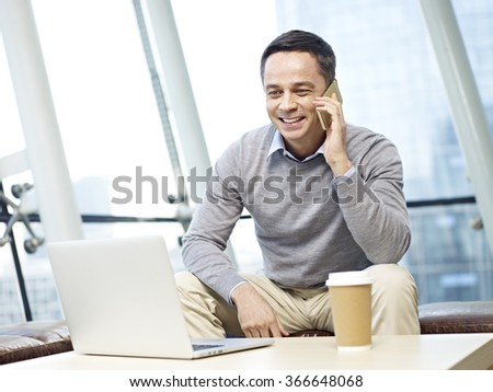 man in business casual wear enjoying a conversation on cellphone in office. - stock photo