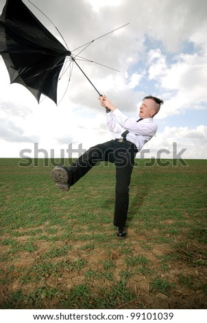 man in business clothing fights with his umbrella outdoors