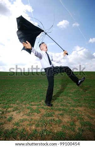 man in business clothing with fights with his umbrella outdoors