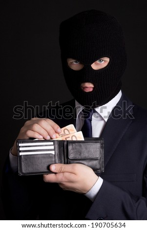 man in business suit and black mask holding leather purse with euro banknotes - stock photo