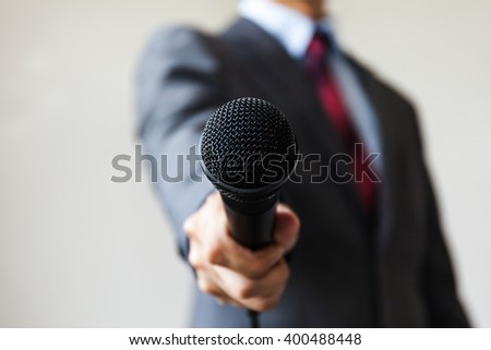 Man in business suit holding a microphone conducting a business interview, journalist reporting, public speaking, press conference, MC - stock photo