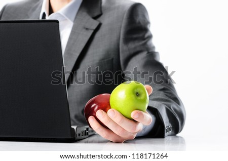 Man in business suit holds bright vibrant red and green apple in hand, symbolising fresh options concepts or healthy lifestyle in the office - stock photo