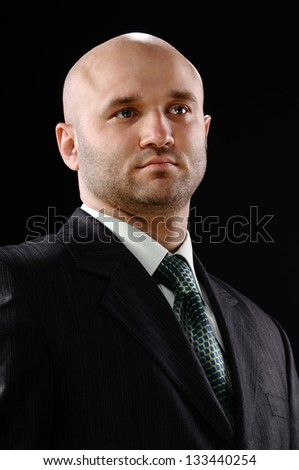 man in business suit standing on a black background