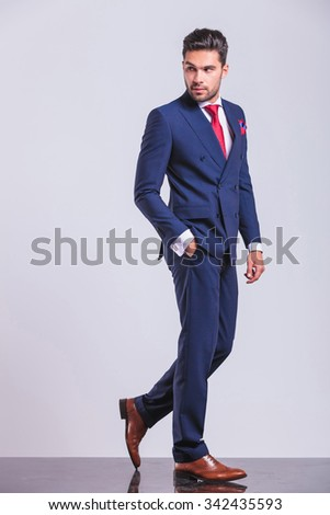 man in business suit walking while looking away with hand in pocket