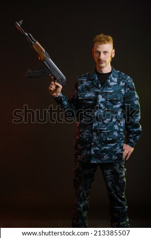 Man in camouflage clothing with a gun