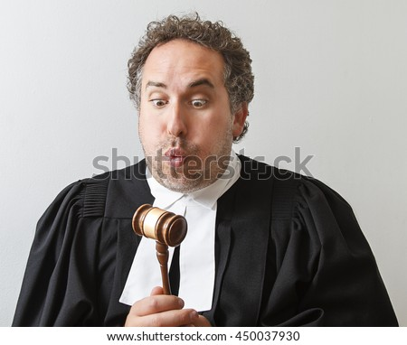 Man in canadian lawyer robe slamming blowing on a gavel - stock photo