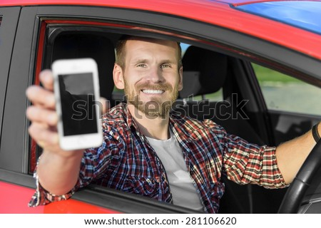 Man in car driving showing smart phone display smiling happy. Focus on model. - stock photo