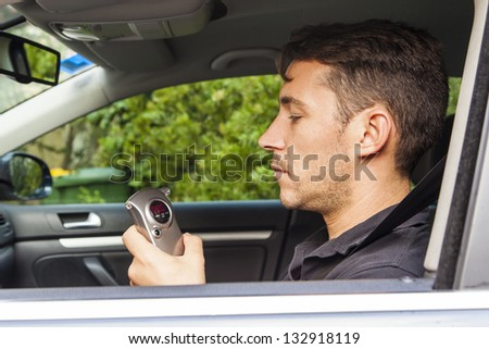 Man in car looking at breathalyzer