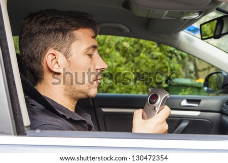 Man in car looking at breathalyzer with 0 reading.