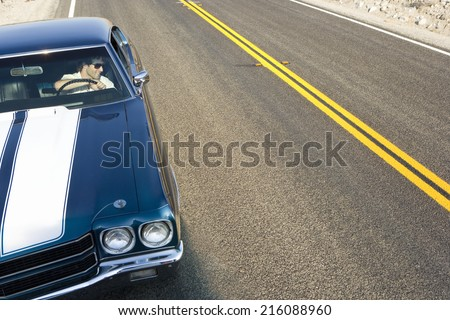 Man in car on side of road, elevated view - stock photo