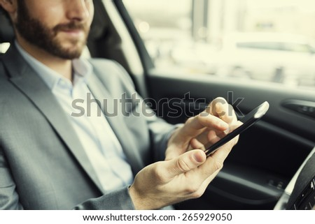 Man in car. Typing text message  on mobile phone - stock photo