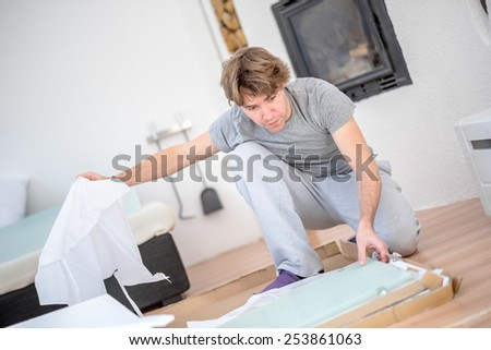 Man in casual clothes kneeling unpacking a package on the wooden floor in the living room at home with an insert wood burner fire in the wall behind him.