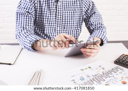 Man in casual shirt using tablet at office desk with business sketch and calculator on white brick background - stock photo
