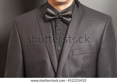 Man in Checkered suit and black  bow tie on gray background