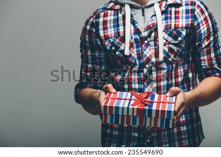 Man in Checkered Top Holding Present with Stripe Design. Captured with No Face. Isolated on Gray Background.