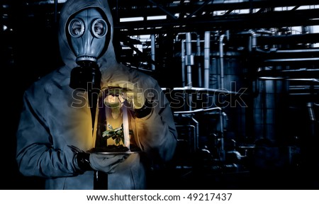 Man in chemical suit with mask holding plant in a portable greenhouse at chemical plant. Earth reflecting on glass - stock photo