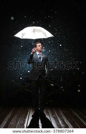 Man in classic suit with  white umbrella in flash lights and rain drops