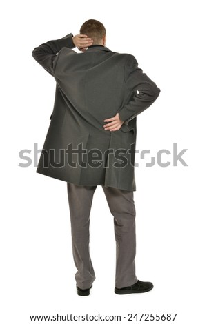Man in coat looking out for something ,full length ,back view on a white background