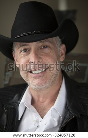 Man in Cowboy Hat Smiling - stock photo