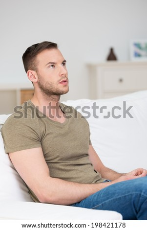 Man in deep thought sitting on a sofa at home staring up into the air with an intense serious expression - stock photo